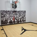 "Millz House SnapSports MN indoor basketball court in Brooklyn Park featuring SnapSports Pro 360 light maple flooring with Michael Jordan wall pad and jump man custom logo_echo panels_60"" backboard"