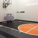 Indoor basketball court by Millz House featuring SnapSports athletic flooring in black and orange