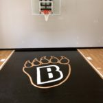 Millz House installed indoor basketball court with SnapSports sport flooring in maple and black with custom team logo