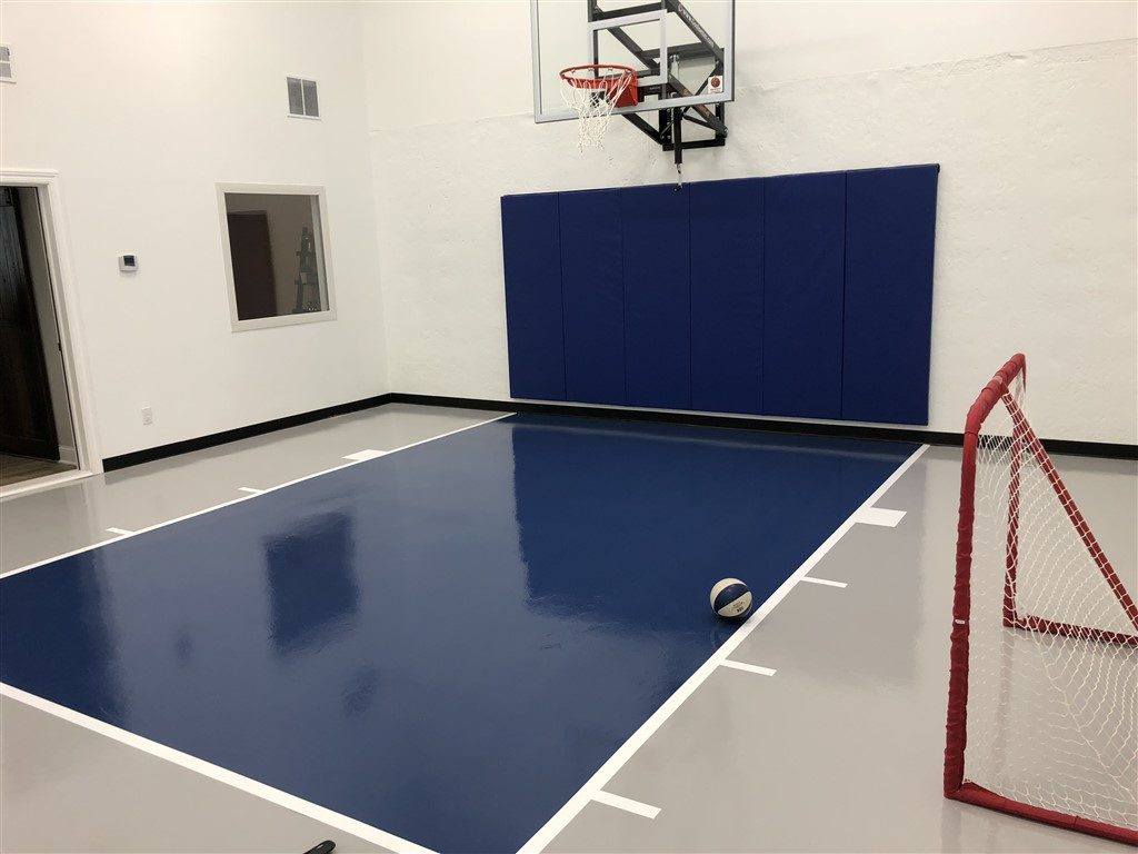 Twin Cities Spring Parade of Homes indoor basketball court featuring an epoxy floor in gray and dark blue installed by Millz House