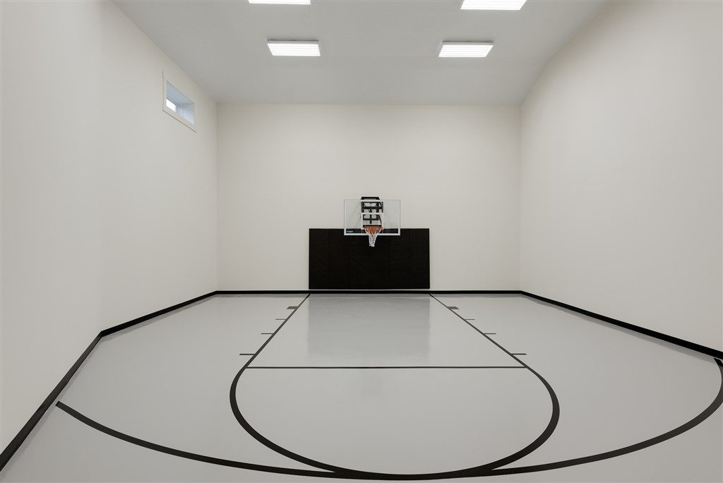 "Millz House installed basketball court featuring white knight gray floor coating, black lines, black wall pads and 60"" adjustable wall-mount hoop"