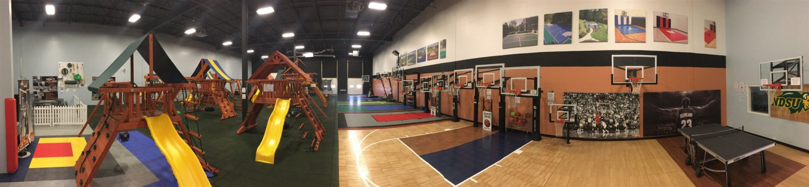 Millz House Showroom in Apple Valley featuring premium wooden swing sets, trampolines, indoor and outdoor game court athletic tiles, basketball hoops